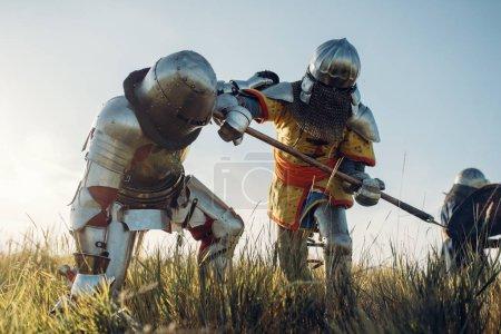 Foto de Caballeros medievales en armadura y cascos luchan con espada y hacha. Blindado antiguo guerrero en armadura posando en el campo - Imagen libre de derechos