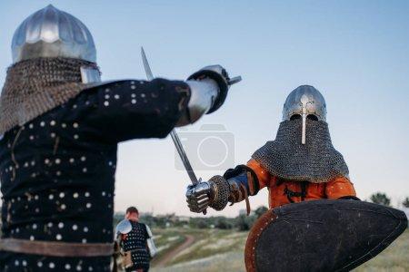 Средневековые рыцари в доспехах и шлемах сражаются мечами. Бронированные древние воины, позирующие на поле боя