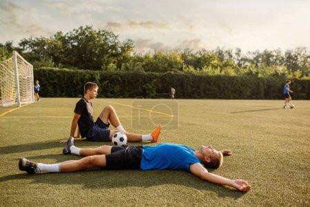 Photo pour Deux joueurs de football masculins reposant sur l'herbe sur le terrain. Footballeurs sur le stade extérieur, entraînement avant le match, entraînement de football - image libre de droit