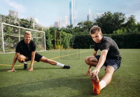 Photo pour Deux joueurs de football masculins faisant de l'exercice d'étirement sur le terrain. Entraînement de football sur le stade extérieur, entraînement en équipe avant le match - image libre de droit