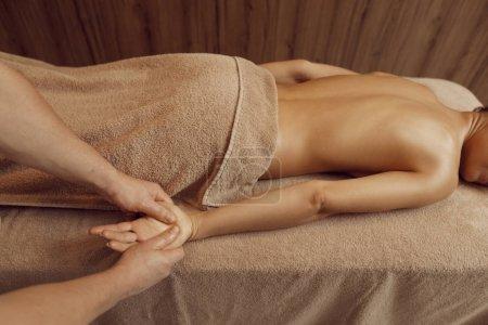 Photo pour Masseur mâle se faisant dorloter les mains d'une jeune femme en serviette, massage professionnel. Massage et relaxation, soins du corps et de la peau. Jolie dame dans le salon de spa - image libre de droit