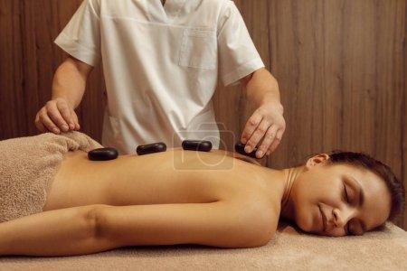 Photo pour Masseur mâle met des pierres sur le dos d'une femme mince dans une serviette, massage professionnel. Massage et relaxation, soins du corps et de la peau. Une jolie dame dans un salon de spa - image libre de droit
