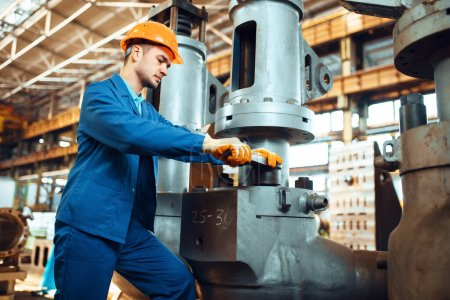 Photo for Engineer in uniform and helmet works on factory. Industrial production, metalwork engineering, power machines manufacturing - Royalty Free Image
