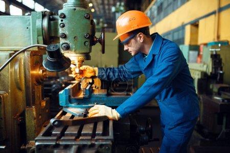 Photo pour Technicien masculin en uniforme et casque travaille sur tour, usine. Production industrielle, génie métallurgique, fabrication de machines électriques - image libre de droit