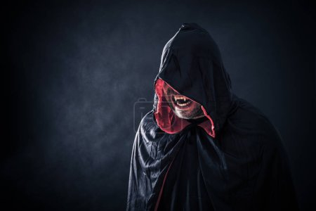 Photo for Angry vampire with red cape showing his scary teeth - Royalty Free Image