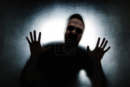 Angry man behind a dusty scratched glass