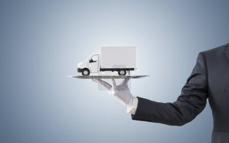 Photo for Businessman offering cargo delivery truck on silver tray - Royalty Free Image