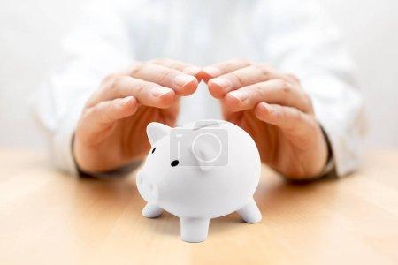 Photo pour Protégez votre argent. Petite tirelire couverte de mains - image libre de droit