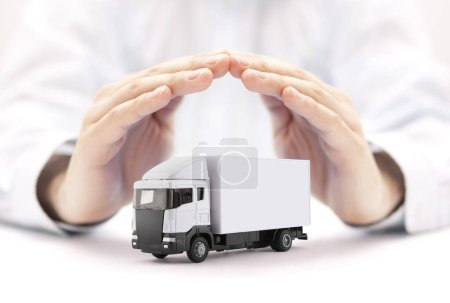 Photo for White cargo delivery truck miniature protected by hands - Royalty Free Image