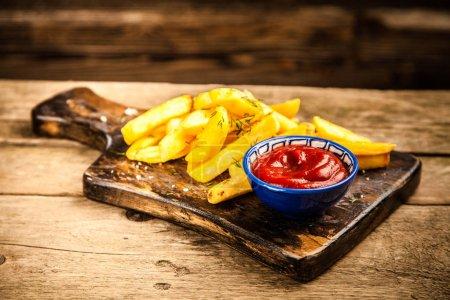 Photo pour Français des frites et du ketchup sur la table en bois - image libre de droit