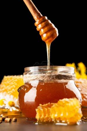 Photo pour Pot de miel et trempette avec du miel qui fuit - image libre de droit