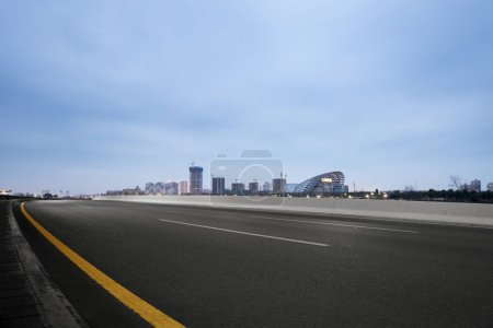 Empty asphalt road with modern city skyline...