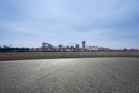 empty asphalt road with modern city skyline