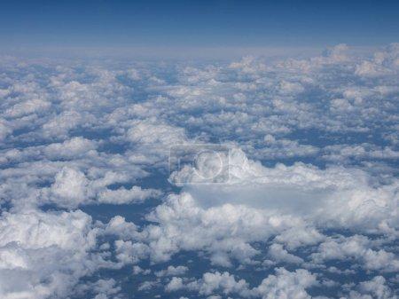 blauer Himmel über Wolken aus dem Flugzeugfenster