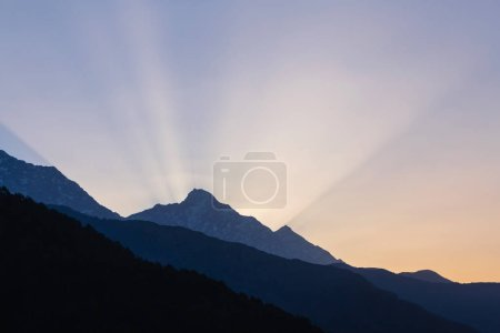 Photo for Rays of rising sun behind mountain in Himalayas, India - Royalty Free Image