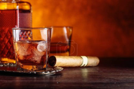 Photo for Glass of scotch whiskey with natural ice and cigar on old wooden table. - Royalty Free Image