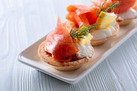 Tartlets with salmon , cream and a slice of lemon on a white wooden table.