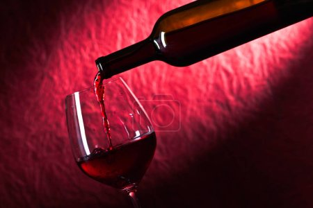 Photo for Bottle and glass of red wine on a dark red background - Royalty Free Image