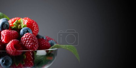 Photo pour Closeup baies assortis mélange de fraises, les bleuets et les framboises sur fond sombre. Espace de la copie de votre contenu. - image libre de droit