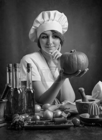 Young beautiful girl in a chef uniform with pumpki...