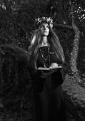 Beautiful young halloween witch wearing vintage gothic dress and holding magical book. Witch in dark forest. Black and white.