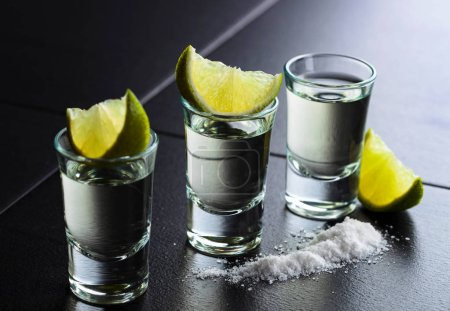 Photo for Small glasses of tequila and lime slices. - Royalty Free Image