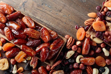 Photo for Various dried fruits and nuts on a old wooden table. Top view. - Royalty Free Image