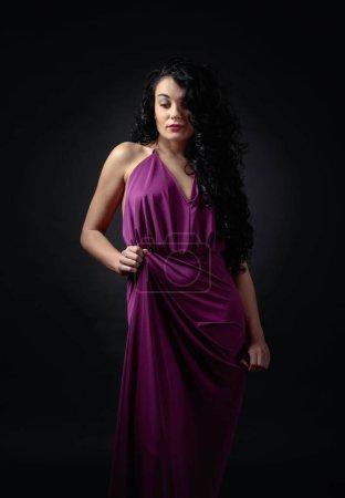 Photo pour Belle jeune femme avec long cheveux bouclés en violet robe de soirée. Portrait de la séduisante brune en robe de soirée longue sur un fond noir. - image libre de droit