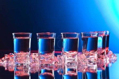 Foto de Vasos de vodka con hielo sobre una mesa de cristal. Luz roja y azul . - Imagen libre de derechos