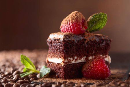 Photo for Closeup of chocolate cake with raspberry and mint on a brown bacground. Sprinkled with cocoa powder. Copy space. - Royalty Free Image