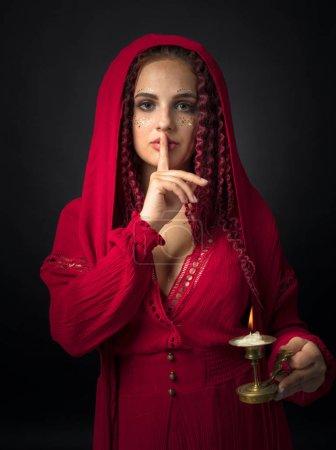 Photo pour Portrait de jeune femme séduisante dans une robe rouge fantaisie avec chandelier en cuivre et bougie allumée. Fille aux cheveux roux ondulés et maquillage . - image libre de droit