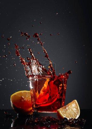 Photo pour Verre à cola avec citron et glaçons tombants sur un fond sombre . - image libre de droit