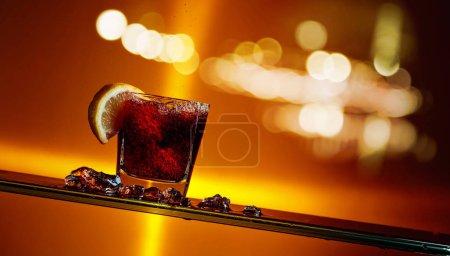 Photo pour Verre de Cola avec tranche de citron. Cocktail au citron sur fond de ville nocturne. Espace de copie . - image libre de droit
