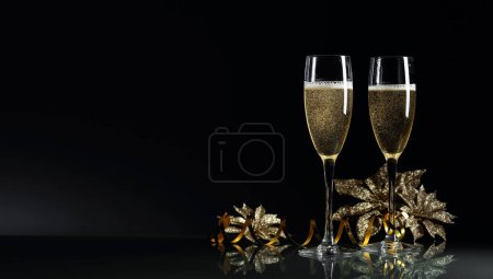 Photo for Two glasses of champagne ready to bring New Year on a black background. Free text space. - Royalty Free Image