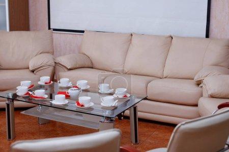 Photo pour Table en verre avec tasses et soucoupes blanches et un canapé beige - image libre de droit
