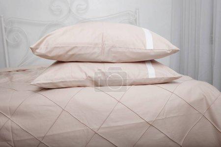 Ropa de cama en la cama hecha con almohadas .