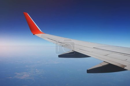 Photo for Airplane wing during the flight above the earth. - Royalty Free Image