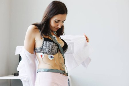 Woman with sensors of holter monitor device for da...