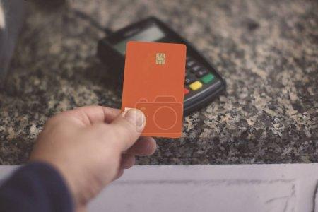 Photo pour La main de l'acheteur avec une carte en plastique orange paie l'achat via le terminal de paiement. Mise au point sélectionnée, fond flou . - image libre de droit