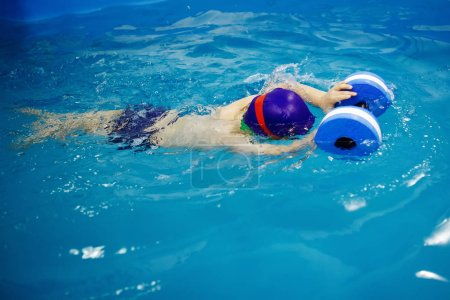 Photo for Three-year-old boy in a blue cap and swimming glasses swims in a pool using a foam toy. Diving. Healthy lifestyle. Aquatherapy. Swimming rehabilitation. - Royalty Free Image
