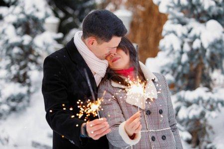 Photo pour Couple heureux d'amoureux avec des étincelles embrasser en hiver sur le fond d'un arbre de Noël en plein air. - image libre de droit