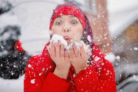 Photo pour Femme en rouge souffle la neige de ses paumes en hiver. - image libre de droit