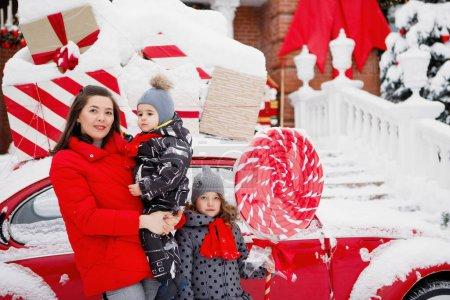 Photo pour Novossibirsk. La Russie. 12.22.2019.Happy famille près de Noël rouge voiture rétro sur le porche de la façade de la maison décorée. Éditorial. - image libre de droit