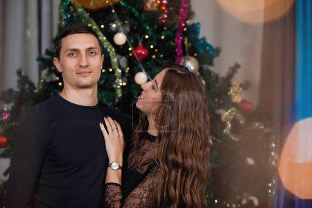 Photo pour Un homme et une femme s'embrassent et se félicitent près d'un arbre de Noël décoré. - image libre de droit