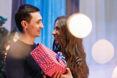 Photo pour Homme et femme avec un cadeau près d'un arbre de Noël décoré. - image libre de droit