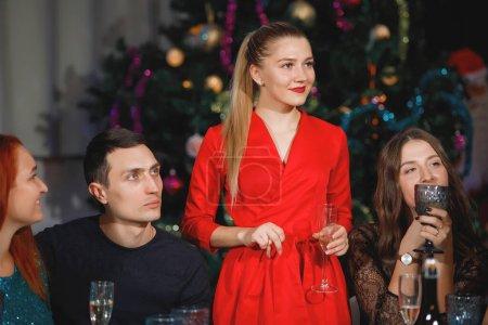 Photo pour Femme blonde en pain grillé rouge à des amis à la table de Noël et du Nouvel An. - image libre de droit