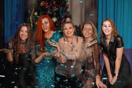 Foto de Grupo de amigos celebra el Año Nuevo con confeti cerca del árbol de Navidad. La gente ríe y se regocija. - Imagen libre de derechos