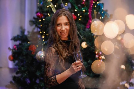 Photo for Beautiful woman having fun with a glass of champagne near a Christmas tree. A woman laughs, smiles, poses. Special vintage noise and grain filter, blurry lights. - Royalty Free Image