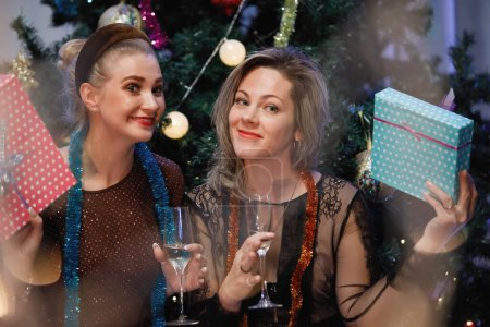 Photo for Two girlfriends give gift boxes to each other near a Christmas tree. - Royalty Free Image