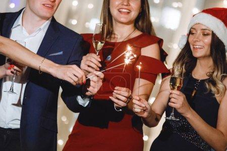 Photo pour Groupe de personnes sont debout avec des verres de champagne et des étincelles pendant les vacances en casquettes et en riant. Concentration sélective et douce. Effet vintage du vieux film. Filtre pour bruit et grain. - image libre de droit